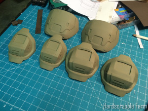 Knee pads, elbow pads, and pauldrons after assembly, Bondo, and a base coat of tan paint.